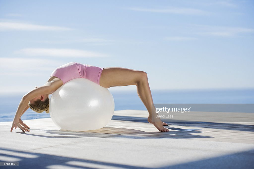 Young woman exercising by sea with fitness ball : Stock Photo