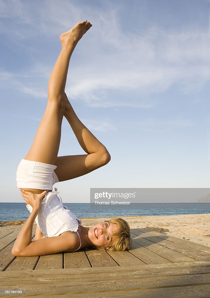 A young woman exercising by the beach