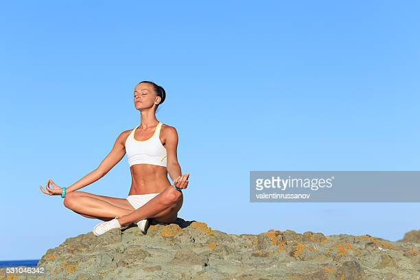 Young woman exercising in lotus position on a rock