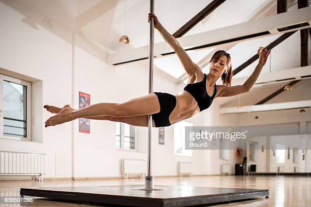 Young woman exercising modern dancing on a pole.