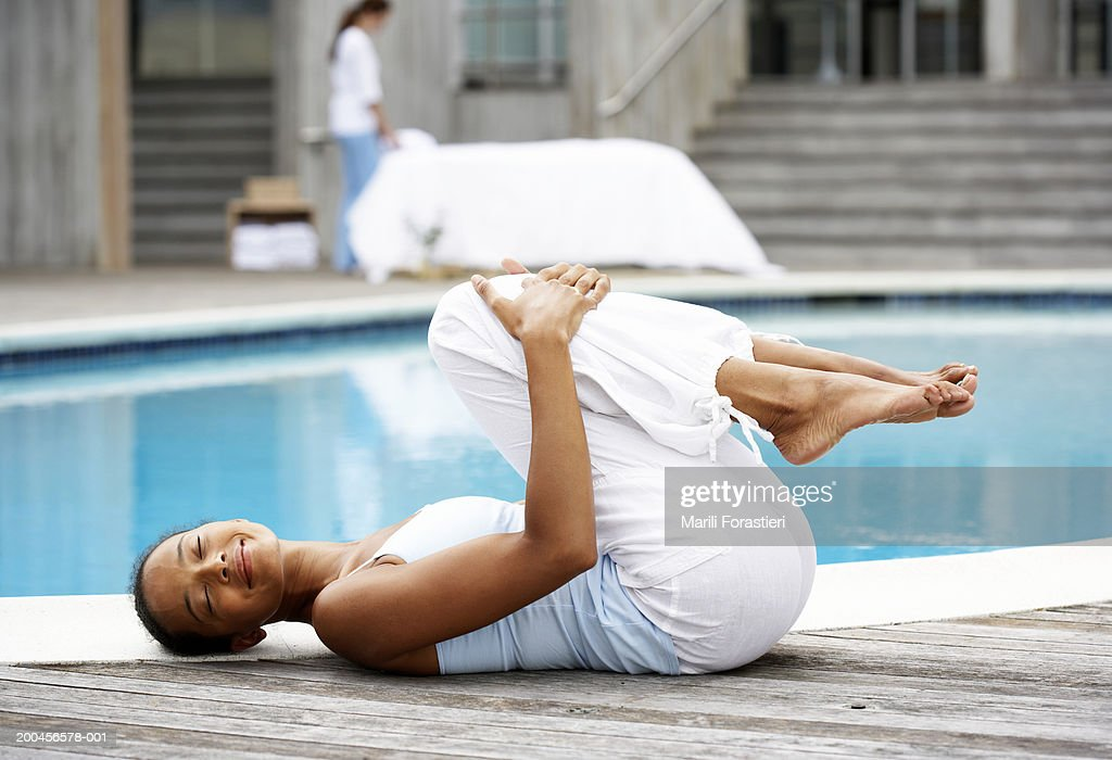 Young woman exercising near pool, smiling, side view
