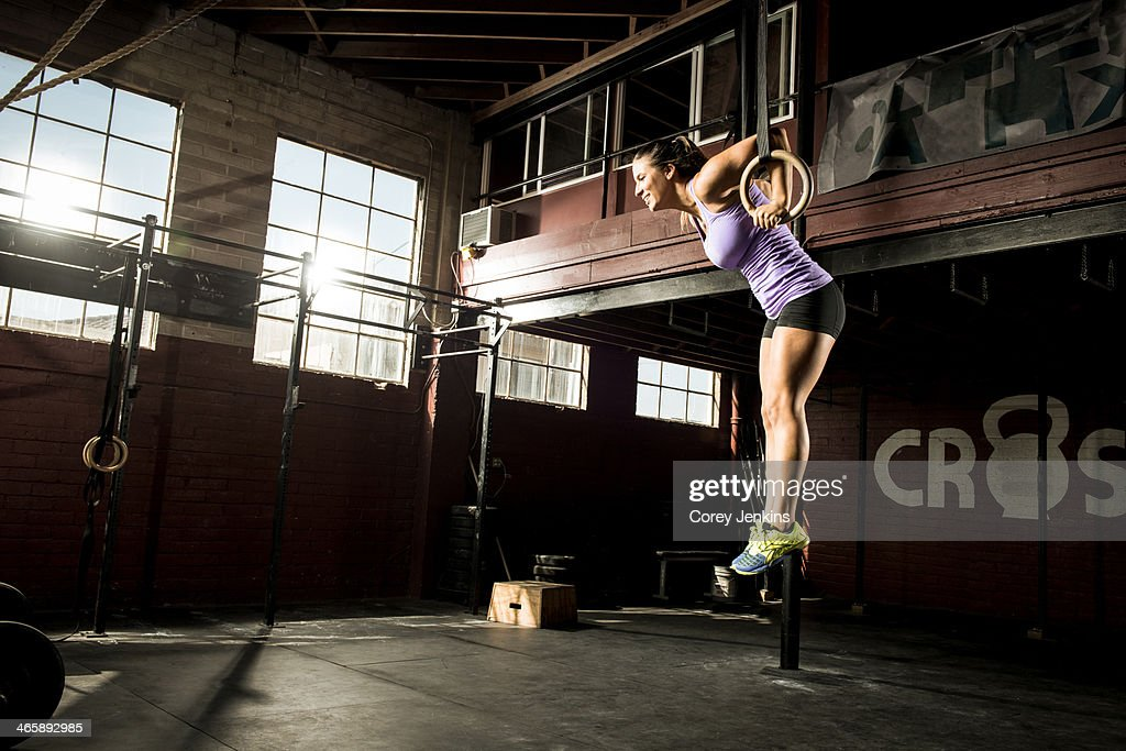 Young woman exercising on gymnastic ring : Stock Photo
