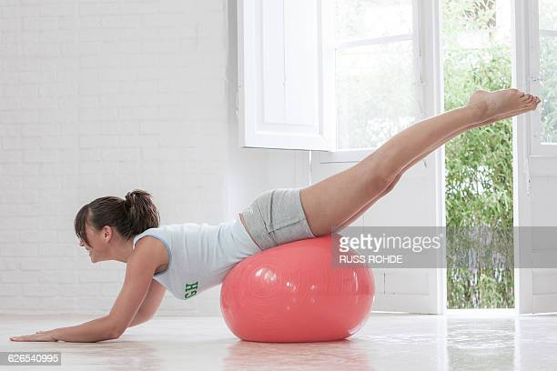 Young woman exercising on pink exercise ball at home