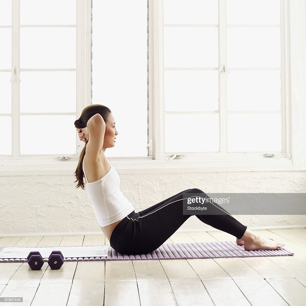 Young woman exercising on the floor : Stock Photo