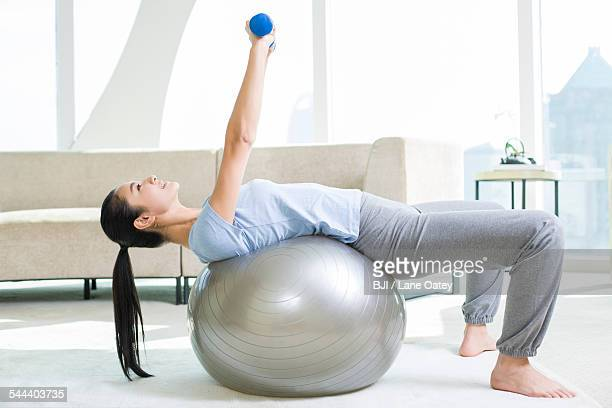 Young woman exercising with dumbbells and fitness ball