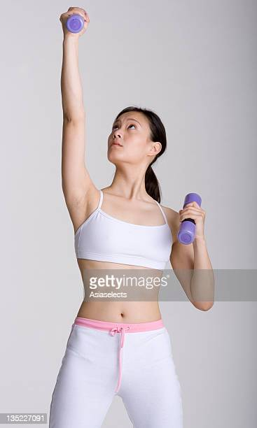 Young woman exercising with hand weights