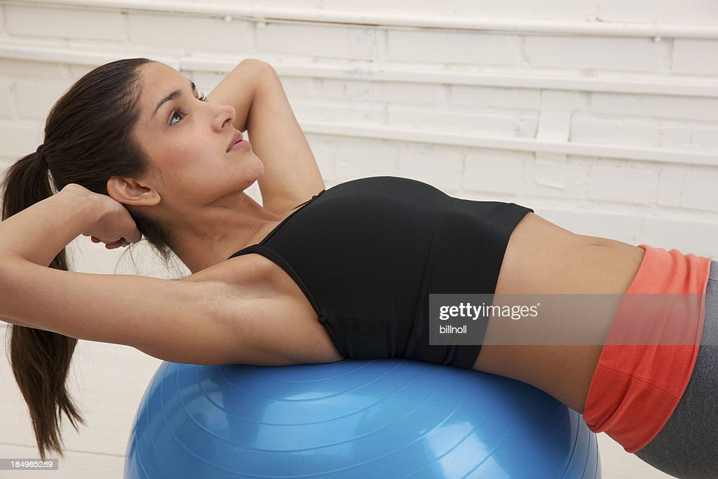 Young woman exercising with inflatable fitness ball