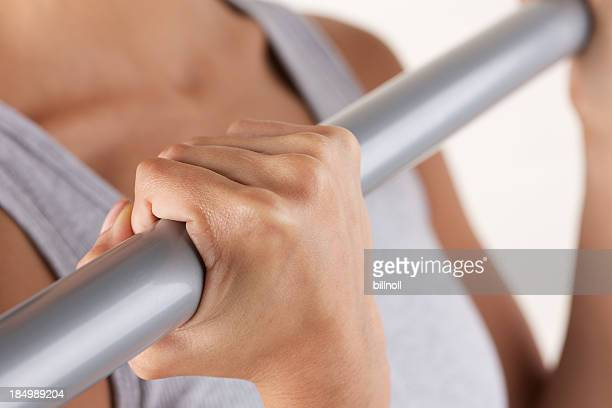 Young woman exercising with metal bar