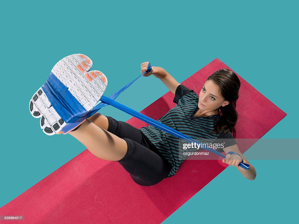 Young woman exercising with resistance bands : Stock Photo