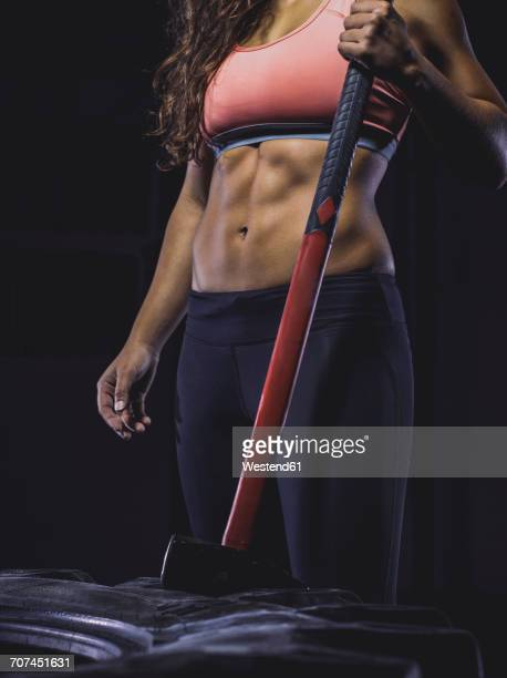 Young woman exercising with sledgehammer and tractor tyre