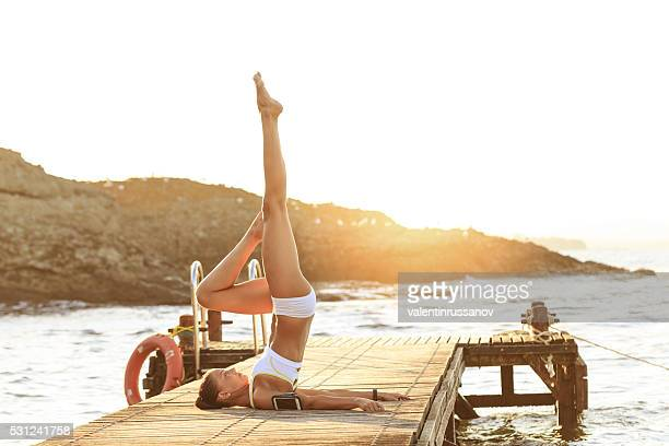 Young woman exercising yoga positions 'candle' on a pier