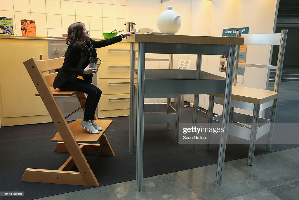 A young woman explores a larger-than-life kitchen in the 'How Children See The World' exhibit in Paul-Loebe-Haus at the Bundestag on April 25, 2013 in Berlin, Germany. The exhibit, which features an over-scaled kitchen complete with a breakfast table, chairs, a kitchen counter, oven and frying pan, marks the 25th anniversary of the Bundestag's Children's Commission and highlights the challenges and the dangers children face in everyday life.