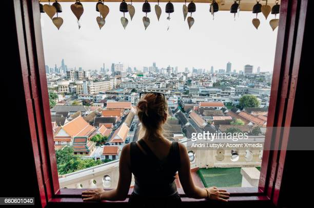 Young woman explores city, looks out from overview