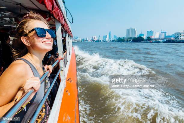 Young woman explores city, looks out from river boat