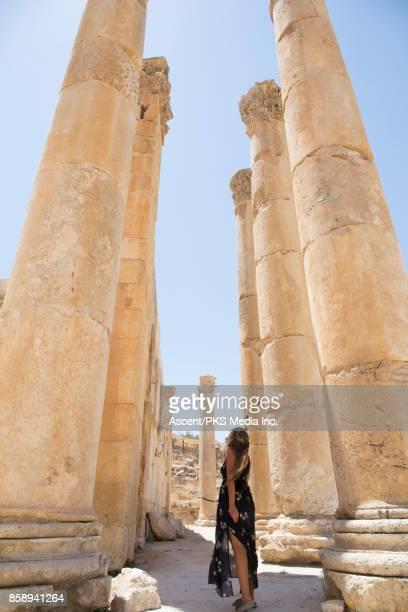 Young woman explores desert ruins from natural corridor