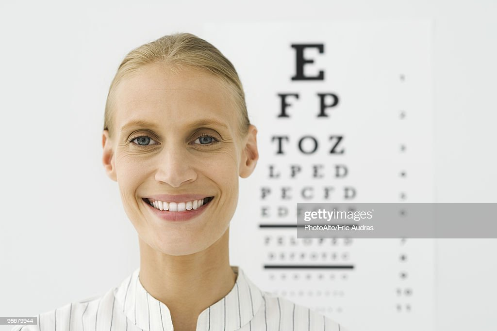 Young woman, eye chart in background, portrait