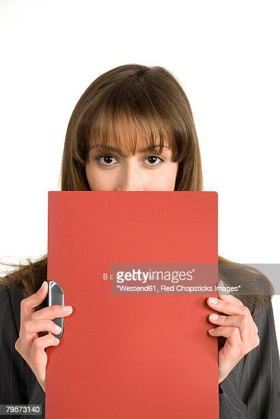 'Young woman, face covered by application file'