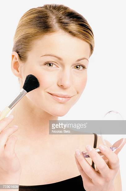 Young Woman face making-up with a brush, close-up (studio)