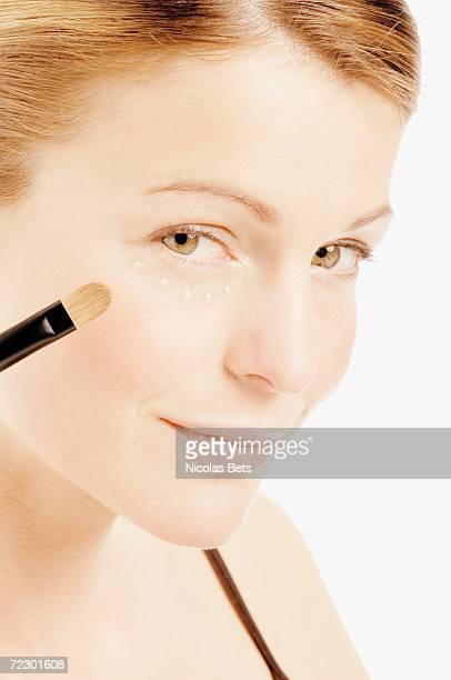 Young Woman face making-up with eyeshadow, drops of cream under her eye, close-up (studio)