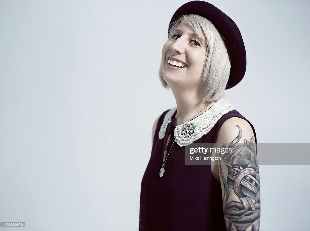 Young woman facing sideways, smiling to camera. : Stock Photo