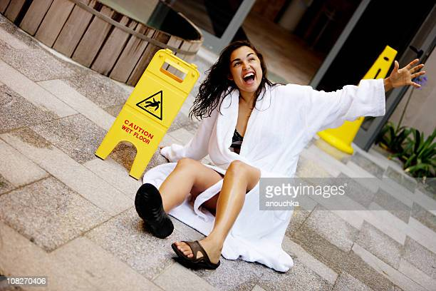 Young Woman Falling on Wet Floor with Caution Signs