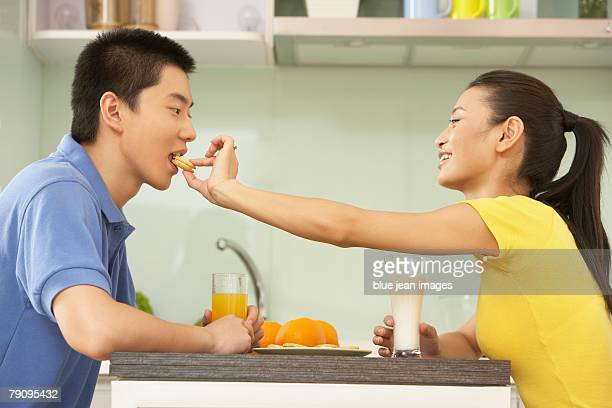 A young woman feeding a young man in the kitchen.