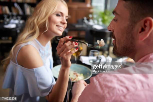 Young woman feeding boyfriend lunch at restaurant table