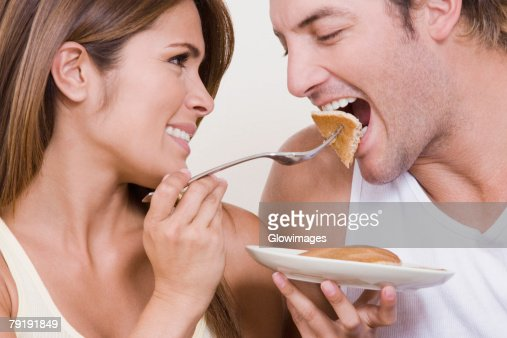 Young woman feeding breakfast to a mid adult man : Foto de stock