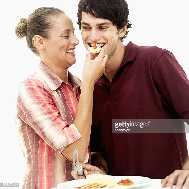 Young woman feeding cheese on a cracker to a young man