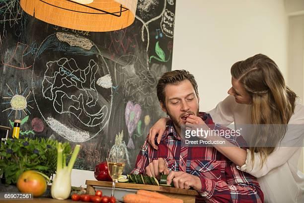 Young woman feeding her husband in kitchen, Munich, Bavaria, Germany