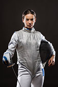 Portrait of Young woman fencer wearing white fencing costume and holding sword and mask. Looking at camera. Black Background