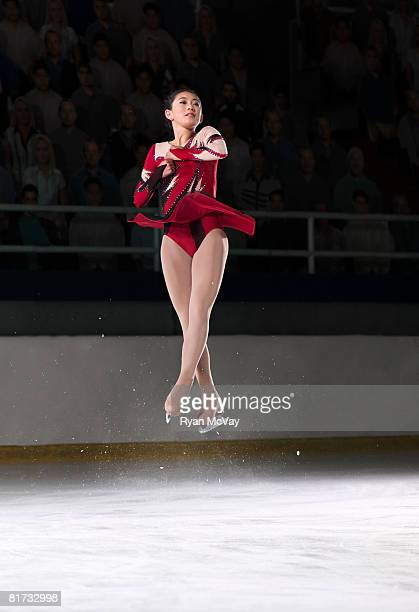 Young woman figure skater mid-air performing a triple axel.