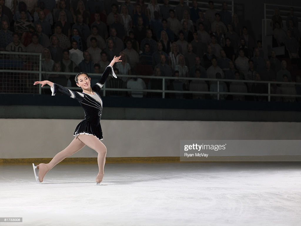 Young woman figure skater standing in finishing pose. : Stock Photo