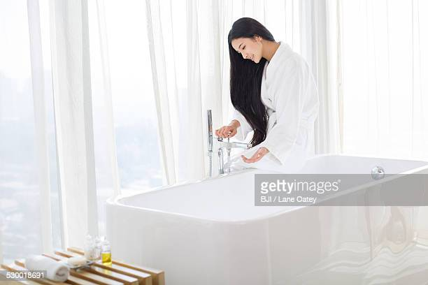 Young woman filling bathtub