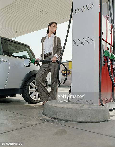 Young woman filling car at petrol station, looking away