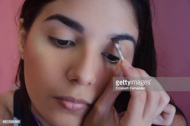 Young woman filling her left eyebrow with makeup.