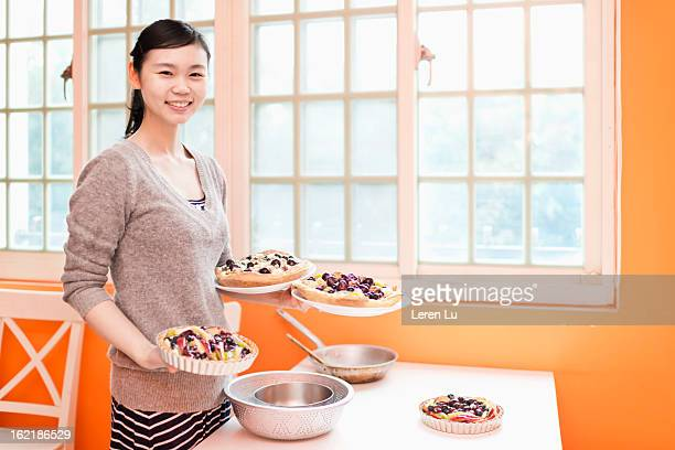 Young woman finished making fruit pies