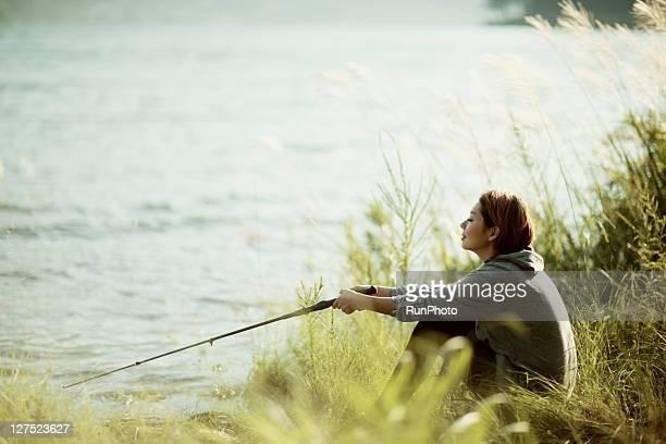 young woman fishing in the lake