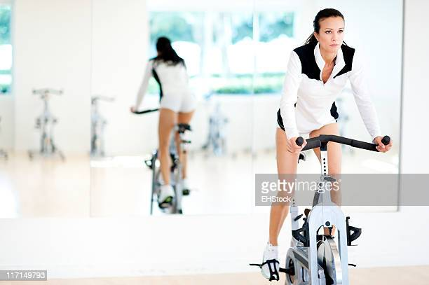 Young Woman Fitness Model Spinning on Staionary Bike in Gym