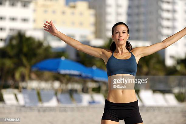 Young Woman Fitness Trainer Jumping on Beach