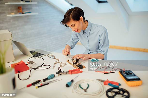 Young Woman Fixing Circuit Board In Her Office.