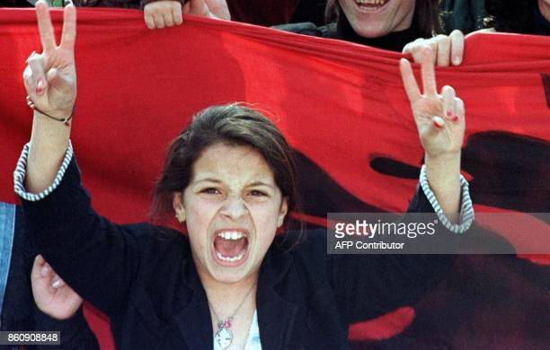 A young woman flashes the Vsign in front of the Albanian flag as some 10000 people stage a demonstration in support of the Kosovo people and NATO air...