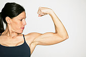 Young woman flexing muscles in studio, portrait