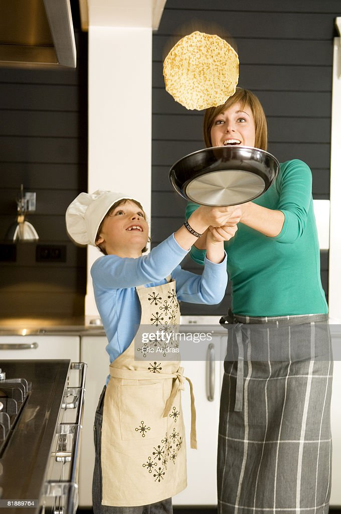 Young woman flipping a pancake with her son : Stock Photo