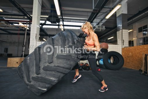 Young woman flipping tire at gym : Stock Photo