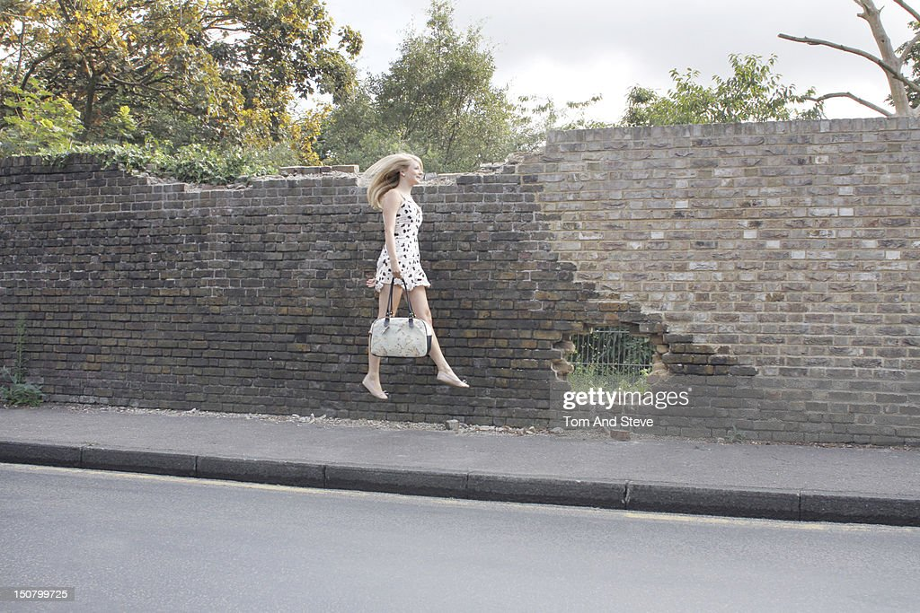 A young woman floating along the street