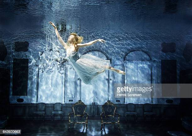 young woman floating gracefully in sunken castle