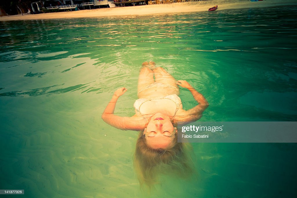 Young woman floating in green water