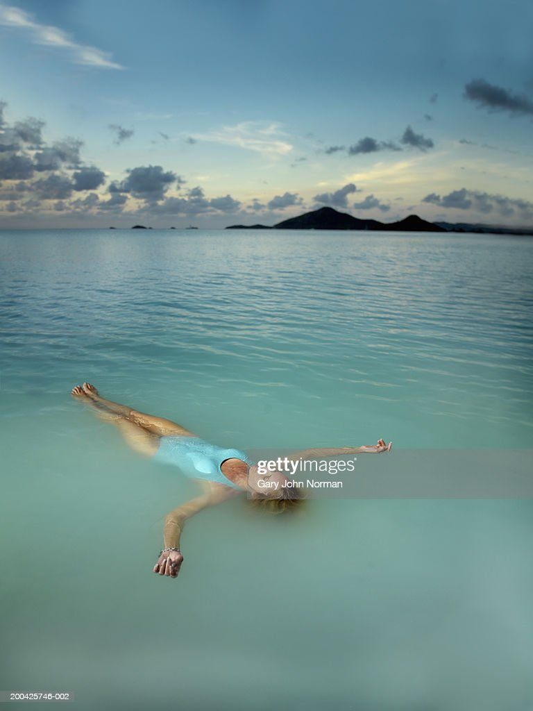 Young woman floating in ocean, elevated view