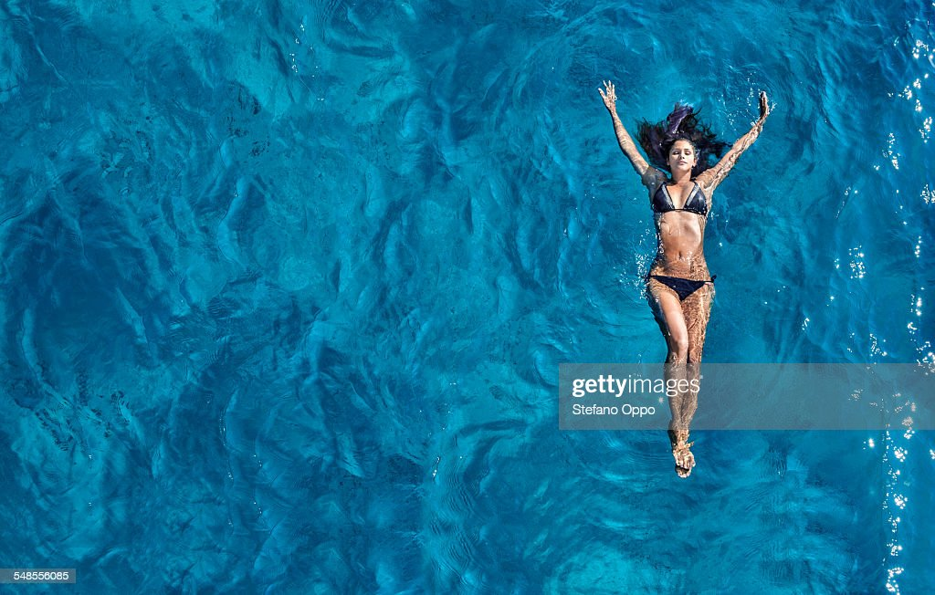 Young woman floating in sea : ストックフォト